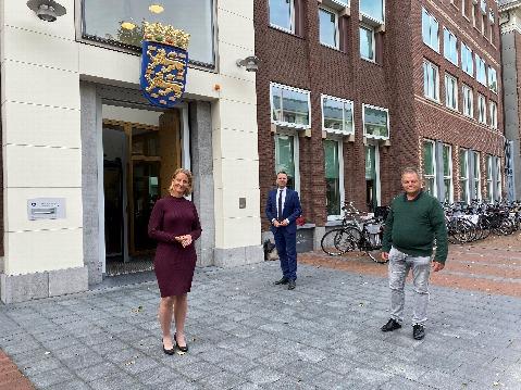 Drie personen poserend voor het provinciehuis
